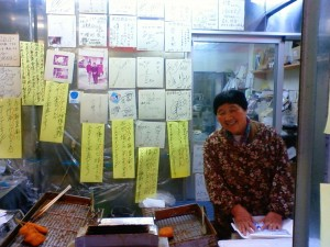人懐っこい笑顔が魅力の岡哲商店のおばちゃん。コロッケ1個80円は1個から購入OKでお味もGOOD!